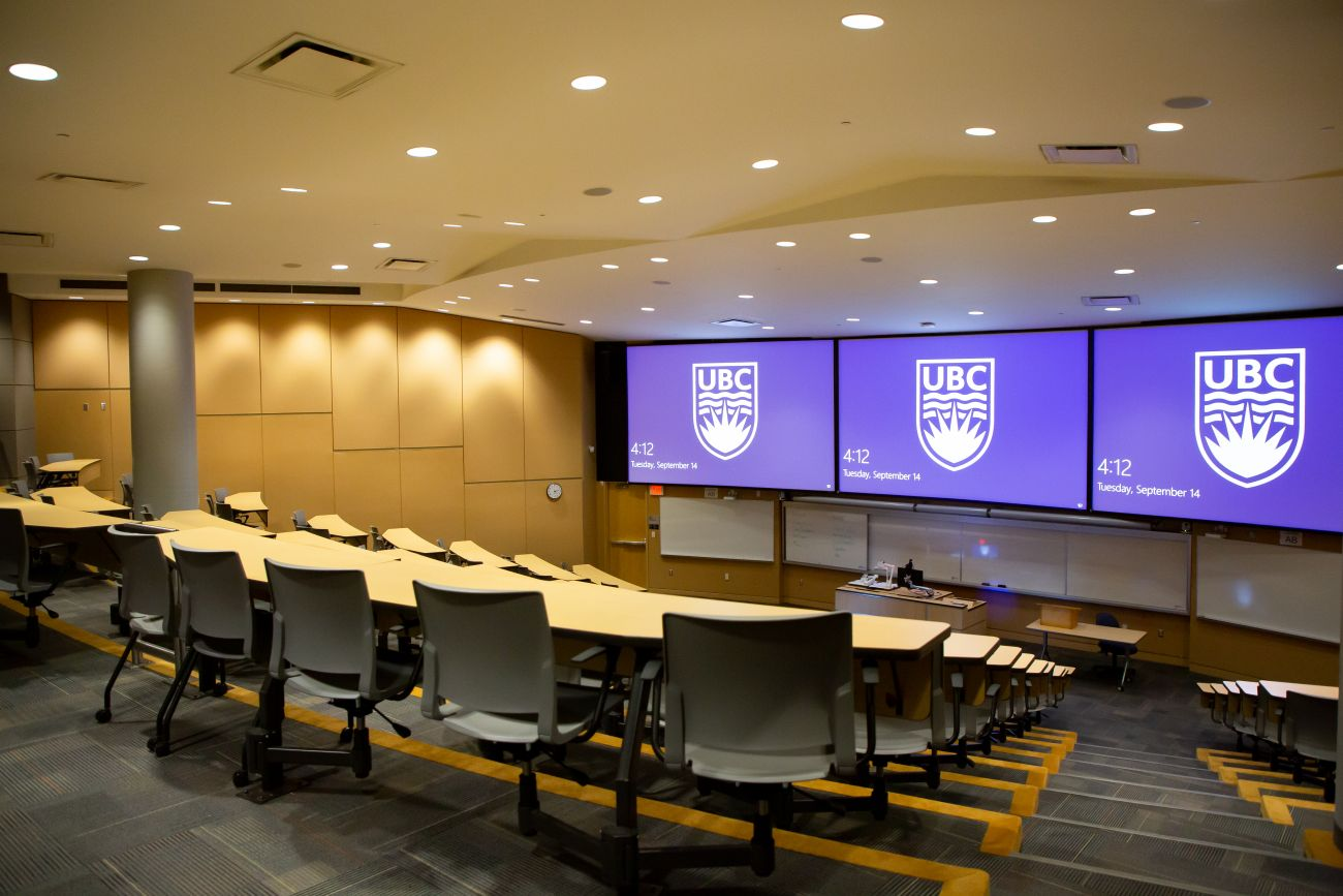 A lecture hall with the UBC logo projected on several monitors